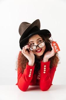 Lächelnde junge kaukasische dame, die hüte durch verkauf trägt