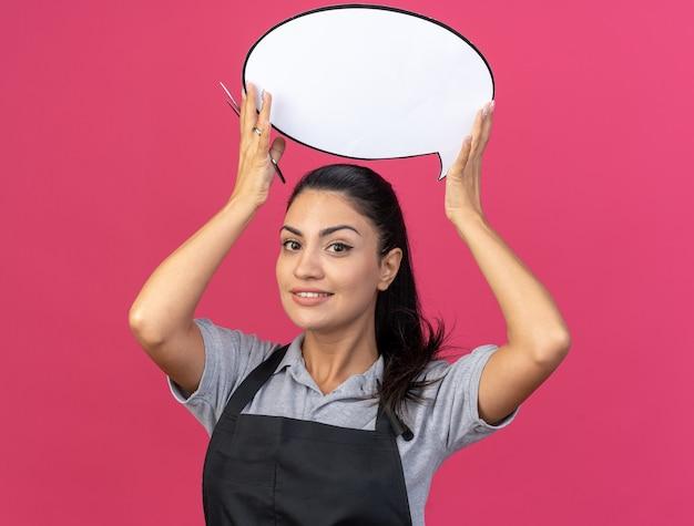 Lächelnde junge kaukasische friseurin in uniform mit sprechblase und schere über dem kopf isoliert auf rosa wand
