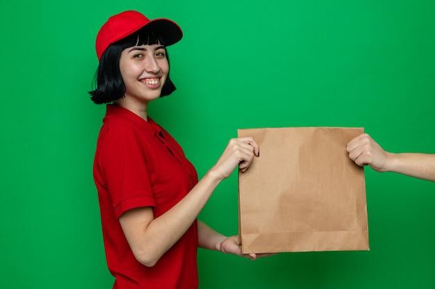 Lächelnde junge kaukasische lieferfrau, die jemandem, der sucht, papierverpackungen für lebensmittel gibt