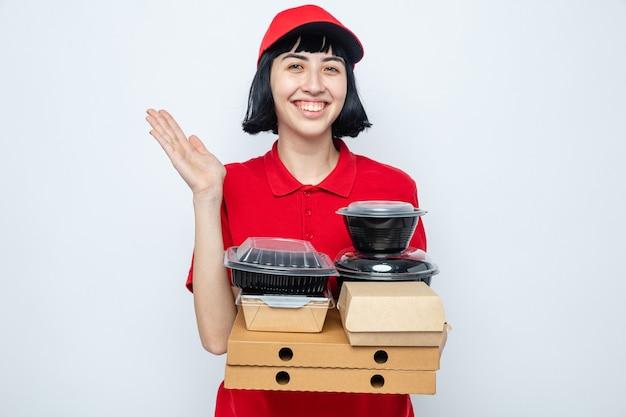 Lächelnde junge kaukasische lieferfrau, die lebensmittelbehälter und pizzakartons hält, die mit erhobener hand stehen