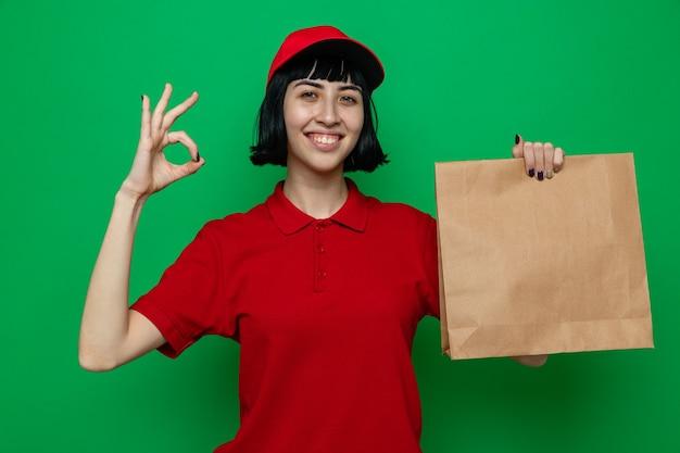 Lächelnde junge kaukasische lieferfrau, die papierlebensmittelverpackungen hält und ok zeichen gestikuliert