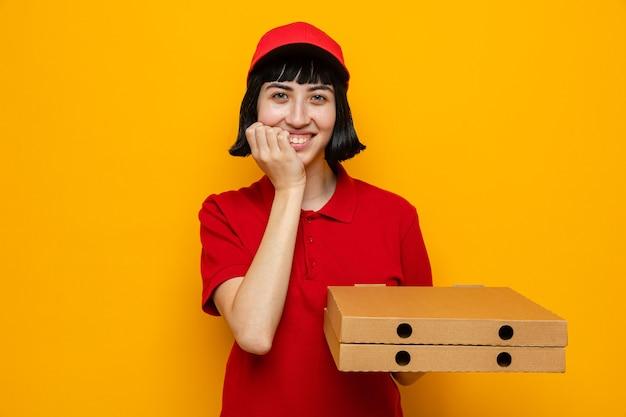 Lächelnde junge kaukasische lieferfrau, die pizzakartons hält und hand auf ihr kinn legt