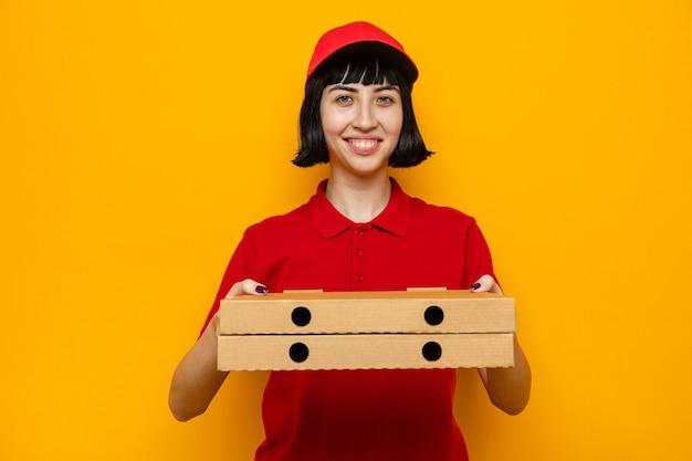 Lächelnde junge kaukasische lieferfrau hält pizzakartons