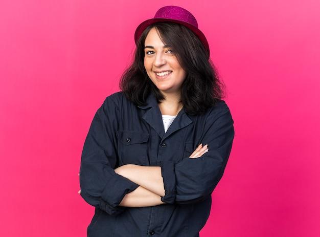 Lächelnde junge kaukasische partyfrau mit partyhut, die mit geschlossener haltung steht und nach vorne isoliert auf rosa wand schaut