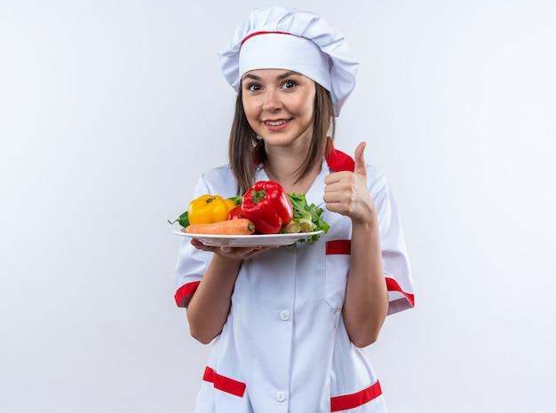 Lächelnde junge köchin in kochuniform, die gemüse auf dem teller hält und daumen nach oben isoliert auf weißer wand zeigt