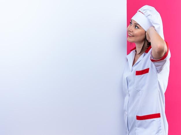 Lächelnde junge köchin in kochuniform steht in der nähe der weißen wand, die auf rosafarbenem hintergrund mit kopienraum isoliert ist