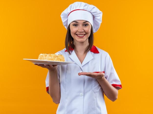 Lächelnde junge köchin mit kochuniform, die mit der hand auf den kuchen auf dem teller auf orangefarbenem hintergrund zeigt