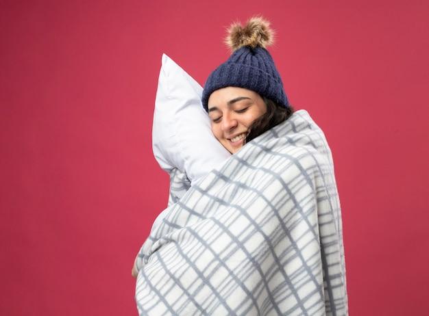 Lächelnde junge kranke frau, die robe wintermütze und schal in plaid gewickelt steht, die in profilansicht umarmendes kissen mit geschlossenen augen, die auf rosa wand lokalisiert stehen
