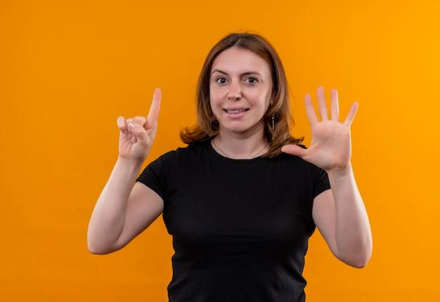 Lächelnde junge lässige frau, die eins und fünf auf lokalisiertem orange raum zeigt