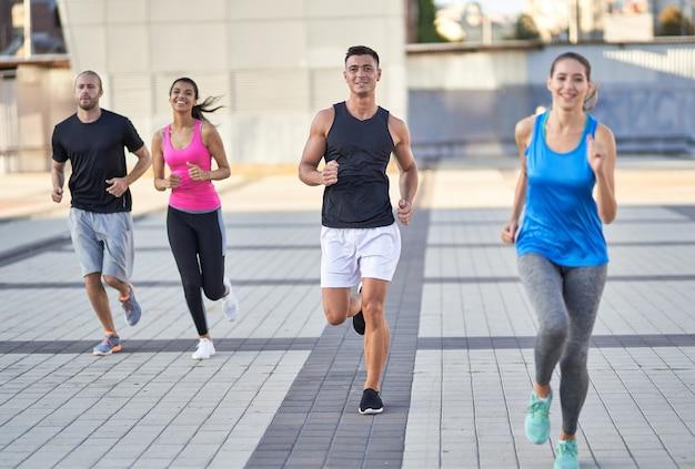 Lächelnde junge läufer, die gemeinsam in der stadt joggen