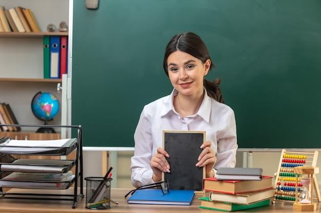 Lächelnde junge lehrerin, die am tisch mit schulwerkzeugen sitzt und eine mini-tafel im klassenzimmer hält