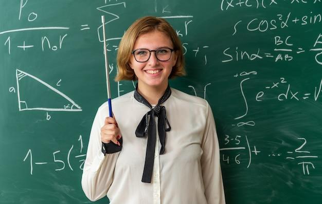 Lächelnde junge lehrerin mit brille, die vor der tafel steht und einen zeigerstock im klassenzimmer hält holding
