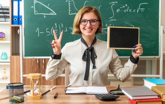 Lächelnde junge lehrerin mit brille sitzt am tisch mit schulmaterial, das eine mini-tafel hält, die eine friedensgeste im klassenzimmer zeigt