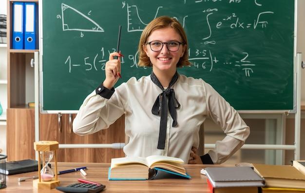 Lächelnde junge lehrerin mit brille sitzt am tisch mit schulmaterial, das einen bleistift hält und die hand im klassenzimmer auf die hüfte legt