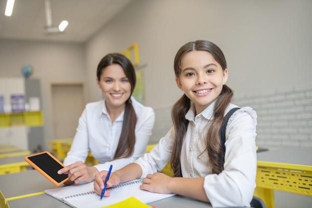 Lächelnde junge lehrerin mit tablette und schulmädchen mit stift und schulheft, die an der schulbank sitzen