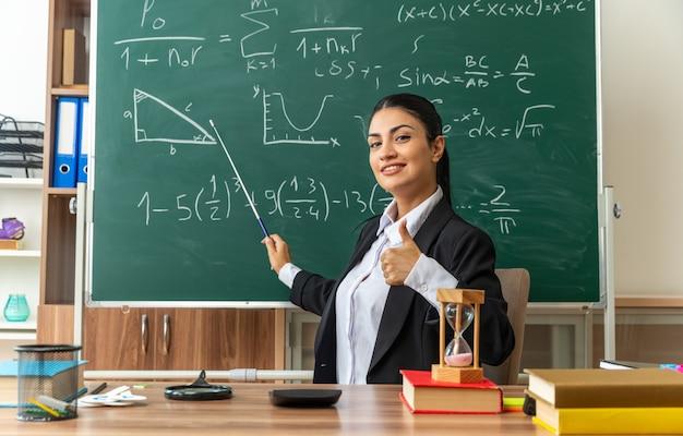 Lächelnde junge lehrerin sitzt am tisch mit schulmaterial punkte an der tafel mit zeiger-stick zeigt daumen im klassenzimmer