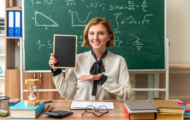 Lächelnde junge lehrerin sitzt am tisch mit schulmaterial und zeigt mit der hand auf die mini-tafel im klassenzimmer