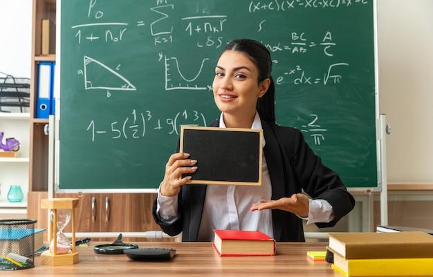Lächelnde junge lehrerin sitzt am tisch mit schulsachen und zeigt auf mini-tafel im klassenzimmer