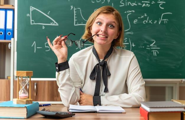 Lächelnde junge lehrerin sitzt am tisch mit schulwerkzeugen und hält eine brille im klassenzimmer holding