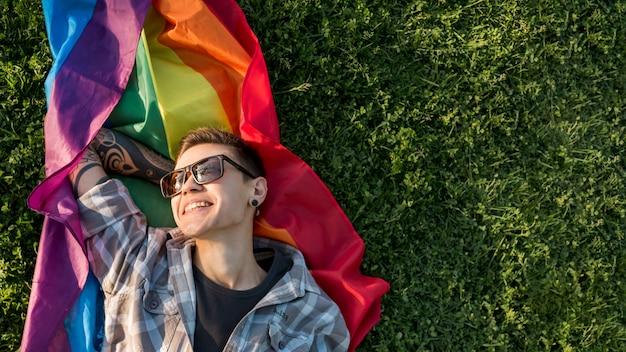 Lächelnde junge lesbe, die auf regenbogenflagge stillsteht