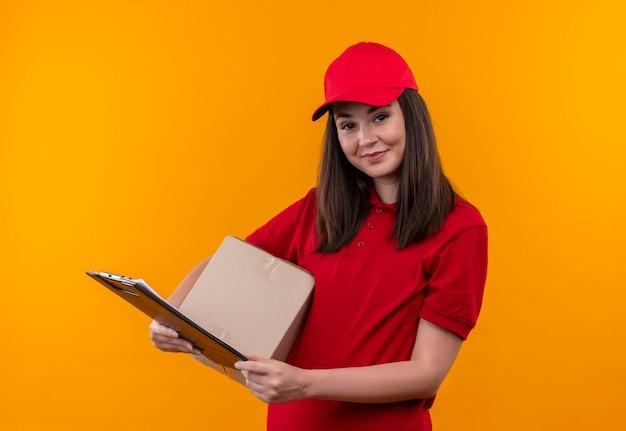 Lächelnde junge lieferfrau, die rotes t-shirt in der roten kappe hält, die eine box und ein flipboard auf isolierter gelber wand hält