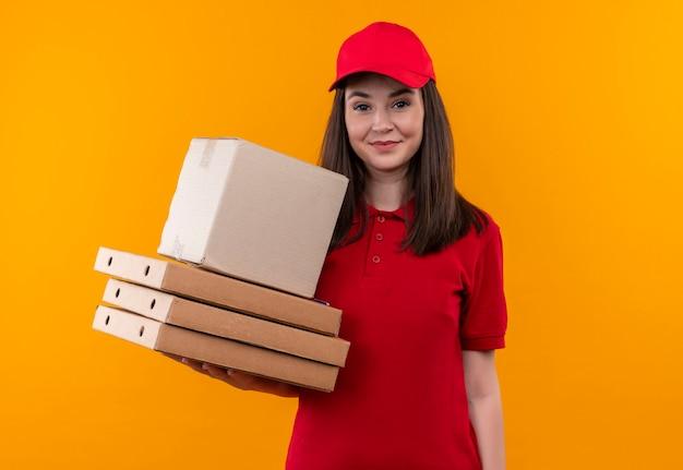 Lächelnde junge lieferfrau, die rotes t-shirt in der roten kappe hält, die eine box und eine pizzaschachtel auf isolierter orange wand hält