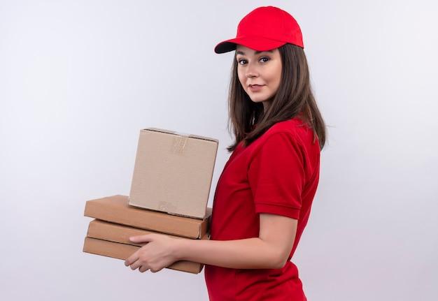 Lächelnde junge lieferfrau, die rotes t-shirt in der roten kappe hält, die eine box und eine pizzaschachtel auf isolierter weißer wand hält