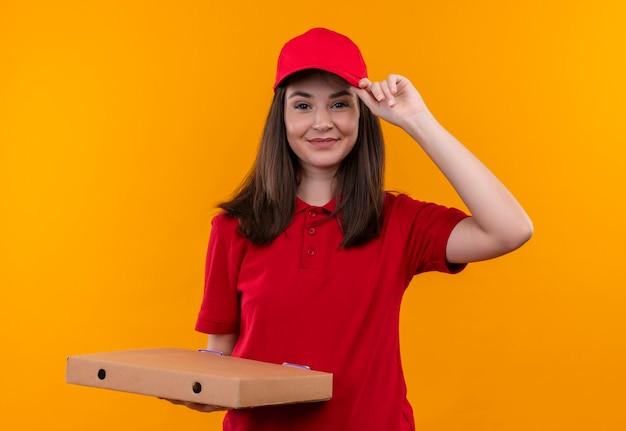 Lächelnde junge lieferfrau, die rotes t-shirt in der roten kappe hält, die eine pizzaschachtel auf isolierter orange wand hält