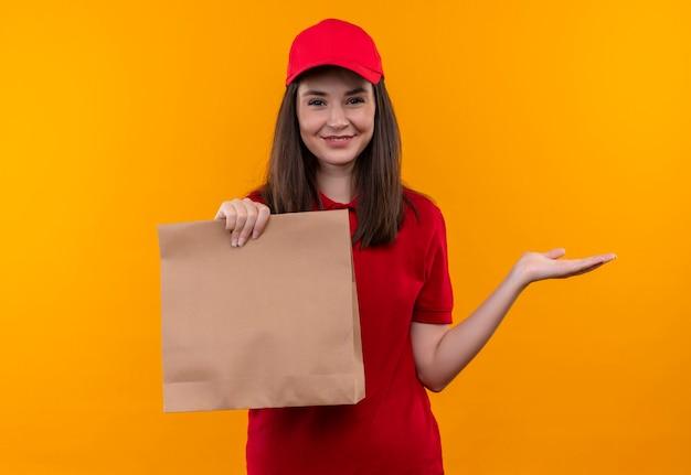 Lächelnde junge lieferfrau, die rotes t-shirt in der roten kappe trägt, die eine tasche auf isolierter orange wand hält