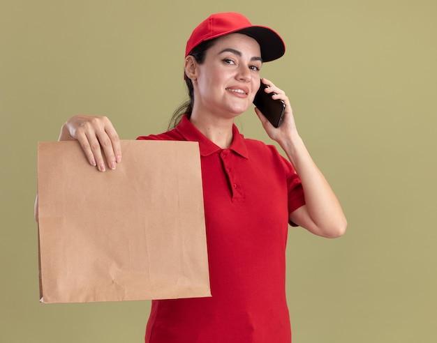 Lächelnde junge lieferfrau in uniform und mütze, die am telefon spricht und papierpaket in richtung kamera ausstreckt