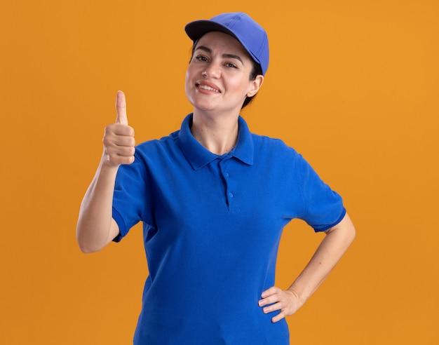 Lächelnde junge lieferfrau in uniform und mütze, die die hand auf der taille hält und den daumen zeigt