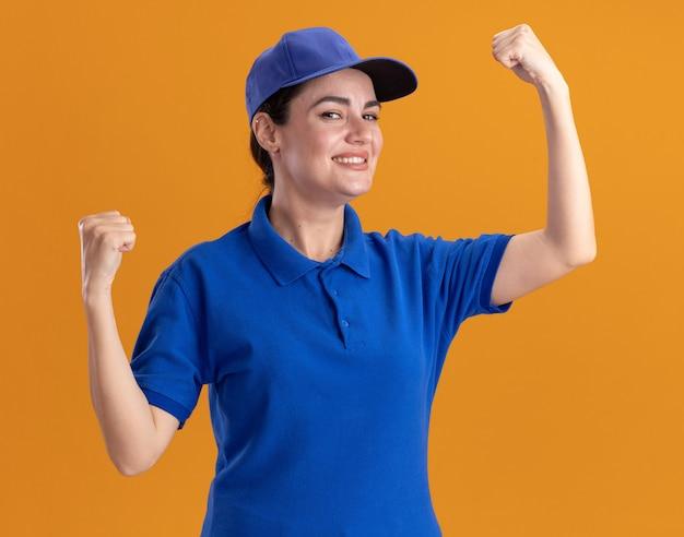 Lächelnde junge lieferfrau in uniform und mütze, die nach vorne schaut und eine starke geste macht, die auf oranger wand isoliert ist?