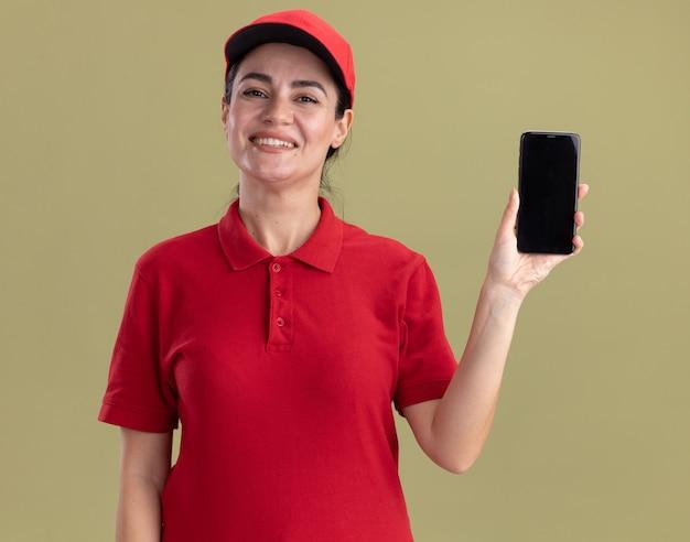 Lächelnde junge lieferfrau in uniform und mütze mit handy zur kamera isoliert auf olivgrüner wand