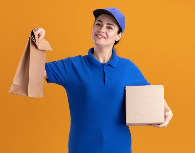 Lächelnde junge lieferfrau in uniform und mütze mit karton und papierpaket isoliert auf oranger wand