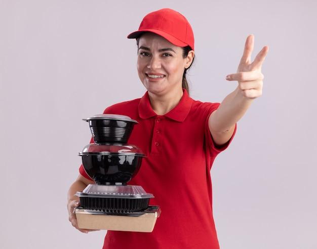 Lächelnde junge lieferfrau in uniform und mütze mit papiernahrungsmittelpaket und lebensmittelbehältern