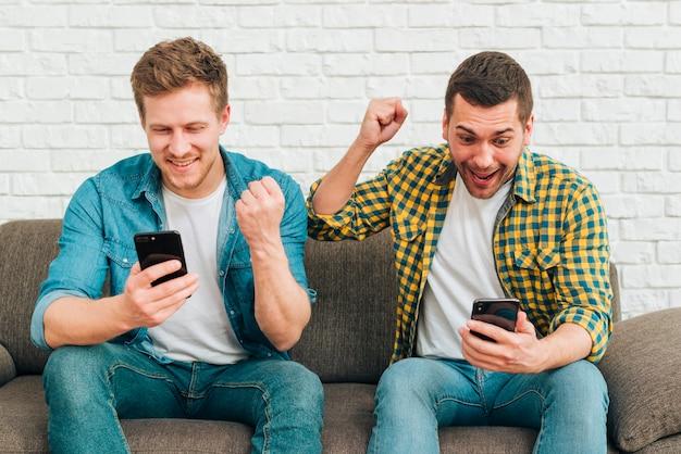 Lächelnde junge männliche freunde, die das intelligente telefon zusammenpreßt ihre faust betrachten