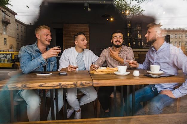 Lächelnde junge männliche freunde, welche die getränke im restaurant genießen