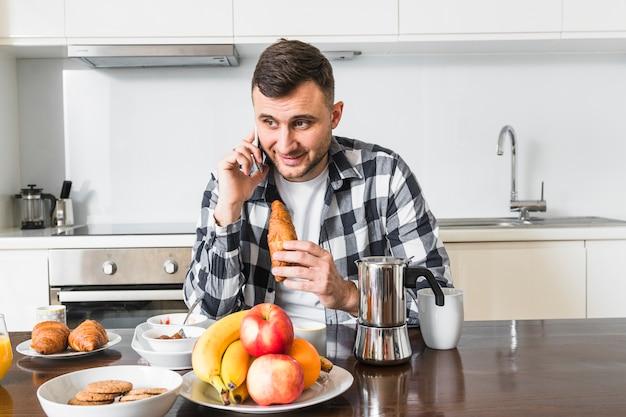 Lächelnde junge mann reden über handy croissant in der hand
