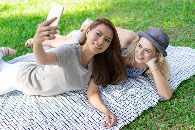 Lächelnde junge multiethnische frauen, die auf decke sich entspannen