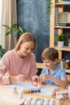 Lächelnde junge mutter, die am tisch sitzt und eier für ostern zusammen mit niedlichem sohn malt