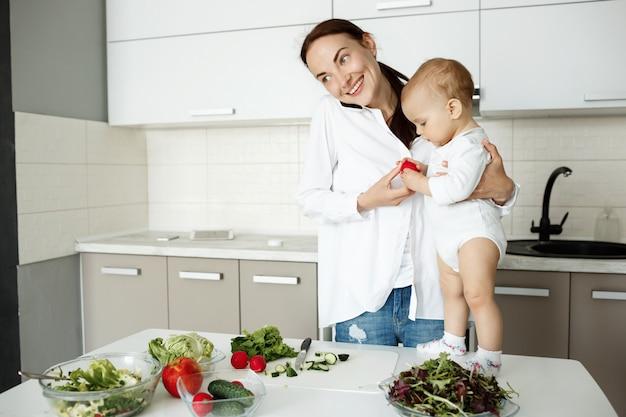 Lächelnde junge mutter, die baby hält, am telefon spricht und gesundes frühstück vorbereitet