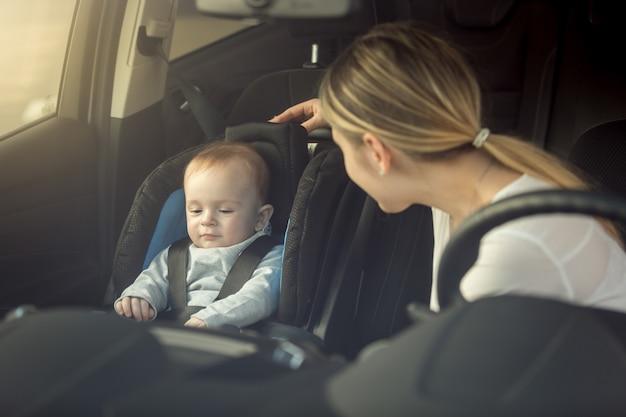 Lächelnde junge mutter, die ihr kind ansieht, das im sicherheitssitz sitzt