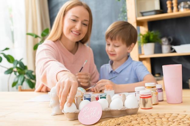Lächelnde junge mutter und ihr sohn sitzen am tisch und genießen es, ostereier zu malen