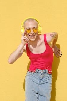 Lächelnde junge nicht-binäre person, die musik mit drahtlosen gelben kopfhörern im freien gegen eine gelbe wand hört. urbanes lifestyle- und technologiekonzept.