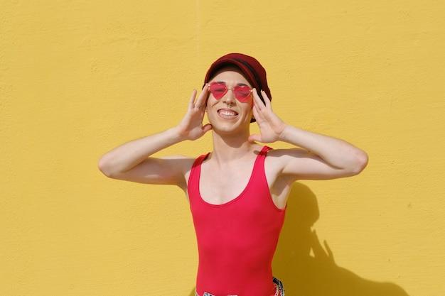 Lächelnde junge nicht-binäre person mit baskenmütze und sonnenbrille, während sie im freien gegen die gelbe wand posiert.