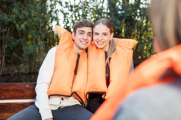 Lächelnde junge paar mit schwimmwesten