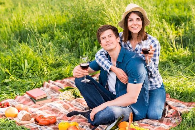 Lächelnde junge paare auf feldpicknick