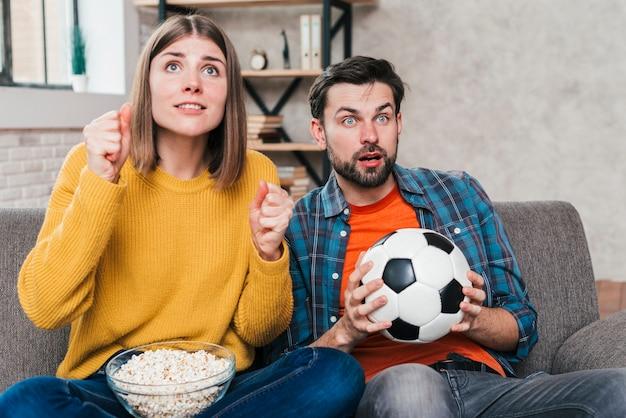 Lächelnde junge paare, die auf dem sofa aufpasst das fußballspiel sitzen