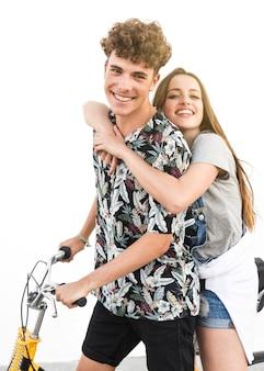 Lächelnde junge paare, die auf fahrrad gegen weißen hintergrund sitzen
