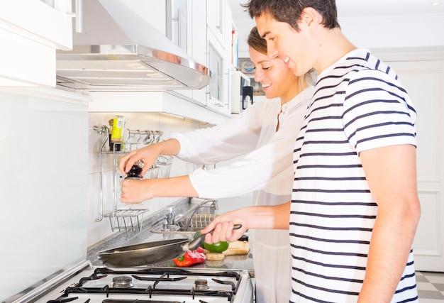 Lächelnde junge paare, die lebensmittel in der bratpfanne über dem küchengasherd vorbereiten